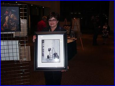 E G Kight holding one of her photographs at the silent auction